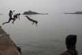 Jumping off a dilapidated jetty near the port in Praia